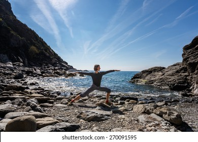 Woman doing yoga on beach in Cinque Terre, Italy