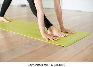 Woman doing yoga on the green mat hands and feet close up warm color