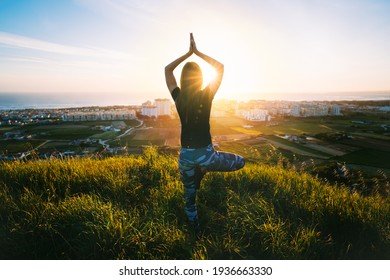 Woman doing yoga on the green grass on the top of the mountain with beautiful view at sunset or sunrise. Tree pose or vrksasana with hands together up above head. Relaxation, harmony with nature