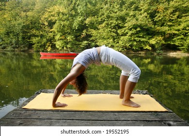 Woman doing yoga on lake in park in autumn