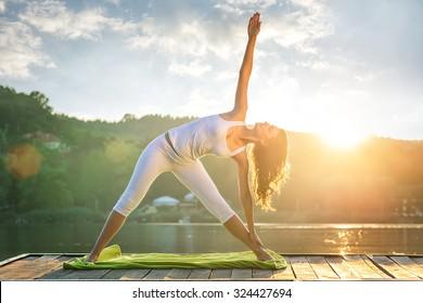 Frau, die Yoga am See macht - schöne Lichter