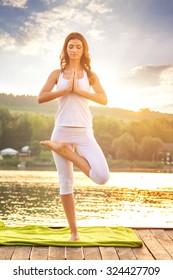 Woman doing yoga on the lake - beautiful lights