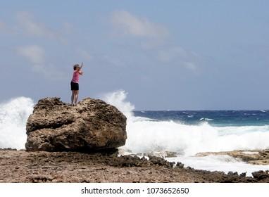 Woman doing Yoga on an Ocean beach as waves break on the shore