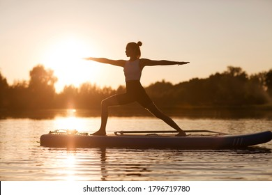 woman doing yoga on sup board at sunset. outdoor summer activity. Sup yoga.  Social Distancing. copy space. Mental Health