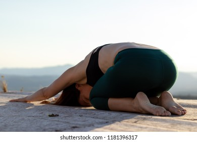 woman doing yoga on the top of a mountain during sunset