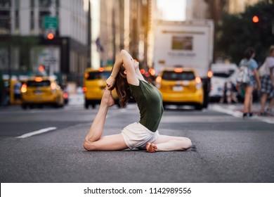 Woman doing yoga pose on city street of New York