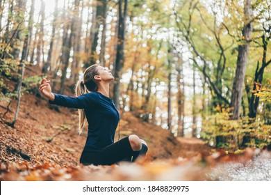 Frauen, die Yoga-Posen in friedlichem Naturwald machen. Lifestyle und Meditation Konzept.