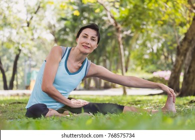 Woman doing yoga pose stretching/meditation at outdoor green park/garden with happy feeling in the morning