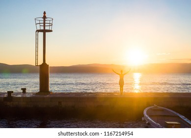 Woman doing yoga position and practicing meditation on a pier on the seaside. Yoga silhouette. Fitness and healthy lifestyle.