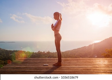 woman doing yoga salutation to the sun Surya Namaskar exercises sequence asan at orange sun up morning high outdoor beautiful view of the island sky sea outside. Namaste hands full body place for text