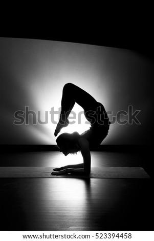 d835fe8d2e833 Woman doing yoga scorpion pose silhouette black and white in studio