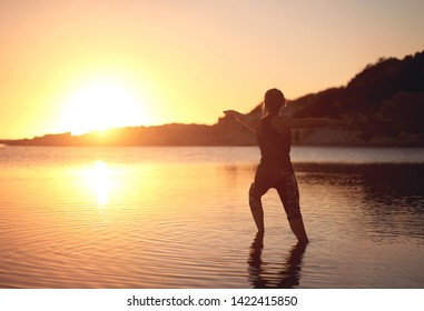 Woman doing yoga in shallow water at the bach during sunset