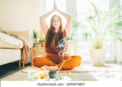 Woman doing yoga at sunny home.