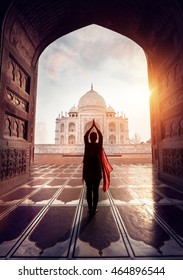 Woman doing yoga tadasana tree pose with flying red scarf in silhouette near Taj Mahal in Agra, Uttar Pradesh, India