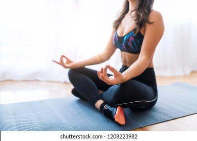 Woman Doing Yoga Twist Mat Healthy Lifestyle. Pretty young girl meditating in the large room. Relaxation at home. Close-up view of young beautiful woman doing morning yoga after waking up at home.