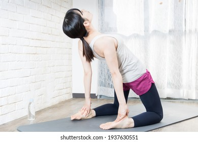 Woman doing yoga while checking the pose