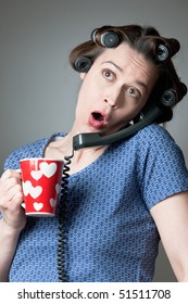 A woman in a domestic role gossiping on the phone with a mug.