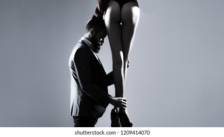 Woman dominates the man, sex games, obeys man. Dominating in the foreplay sexual game. Luxury ass, huge butt, sexual forms. Legs of woman in shoes at man with beard. Love and relations, dominating.
