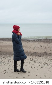 Woman in a down jacket and hat walks near the sea