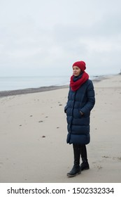 Woman in a down jacket and hat walks on the seashore