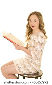 A woman with down syndrome, holding onto a book, with a shocked expression.