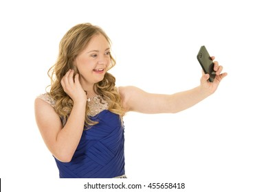 A woman with down syndrome holding out her phone taking a picture, with a big smile