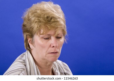 woman with a downcast look on blue background
