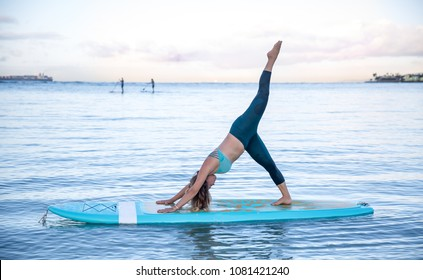 Woman in downward dog pose SUP Yoga practice sunrise in Waikiki