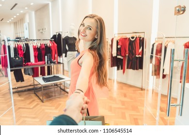 Woman dragging her man to fashion shopping in boutique or store by the hand