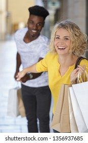 woman dragging her reluctant boyfriend shopping