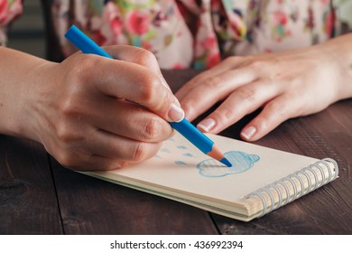 Woman draw blue rain in notebook. Weather symbol concept