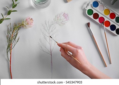 Woman drawing flower on album sheet