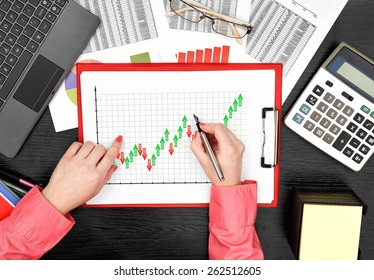 woman drawing forex chart on clipboard sitting in office