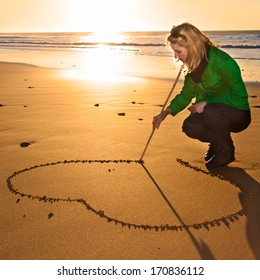 Woman drawing a heart shape in the sand during the pleasant walk along the beach on a cold sunny winter day. Out off season beach leisure activities.