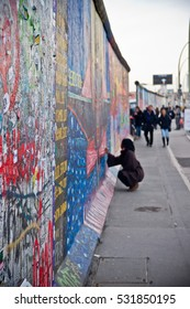 Woman drawing on the street art painted Berlin wall