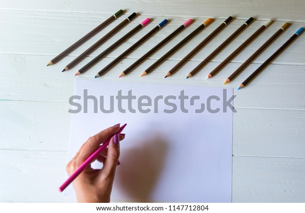 Woman is drawing on a white paper. Tools for drawing,