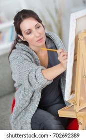 woman drawing pencil portrait on floor in workshop