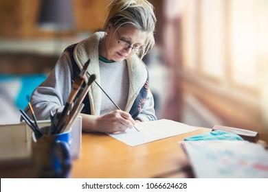 Woman is drawing picture by brush and paint