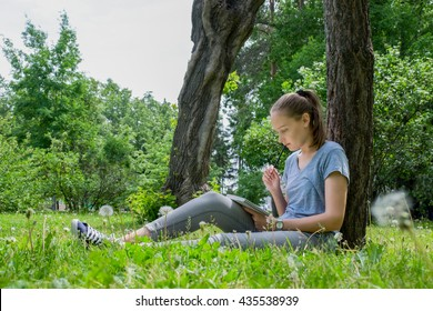 Woman draws sitting on a grass in the daytime