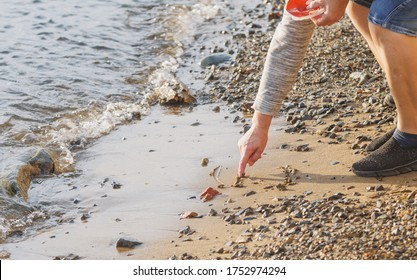 Woman draws a something by finger on the sand.