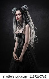Woman with dreads and black gothic dress posing on dark background