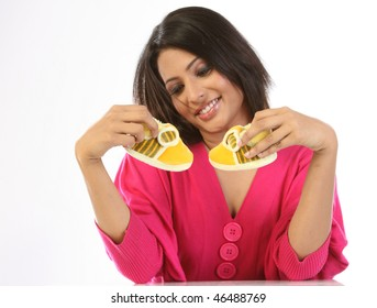 Woman dreaming holding her small baby shoes