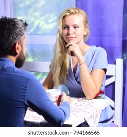 Woman and dreamy face and man have a date. Rendezvous and coffee break concept. Couple in love holds cups of coffee at table. Girl with blond hair and bearded guy on light cafe background