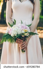 woman in dress with bouquet close up