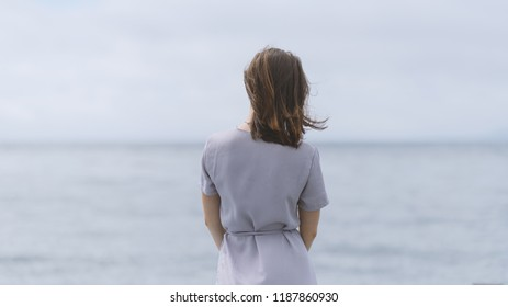 Woman in dress enjoys a walking near the sea shore. View from back.