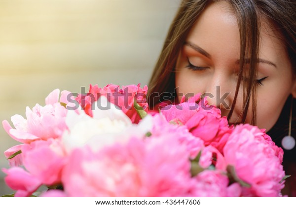 Woman in dress with flowers peonies outdoors