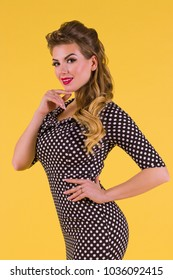 Woman in dress with hairdo stands in yellow studio, pin up style