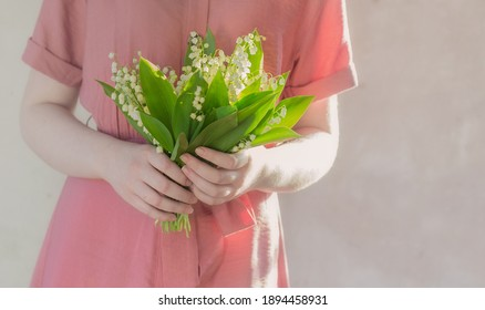 woman in dress holding bouquet of lily of valey on background old wall