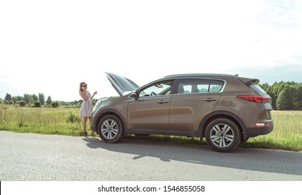 woman in dress on road, makes phone calls, crossover car, an open hood, problem on road, broken car, tow truck call, ambulance, police and emergency services. In summer, outside city on highway
