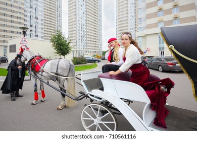Woman in dress poses in coach with coachman girl near buildings, man stands near horse